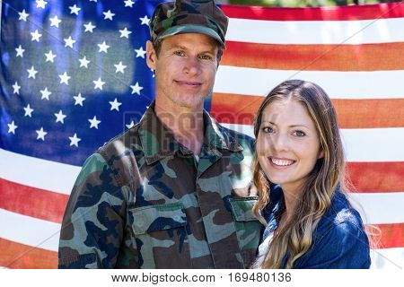 Portrait of american soldier reunited with his partner in front of american flag