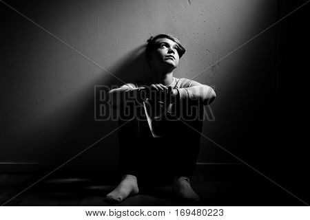 Barefoot Thoughtful Boy Sat Against Wall