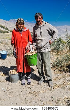 Woman And Man With Bucket In Tajikistan