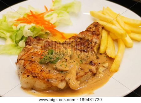 closeup grilled porkchop with mushroom on white plate