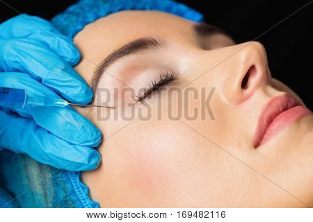 Woman receiving  injection on her forehead in examination room