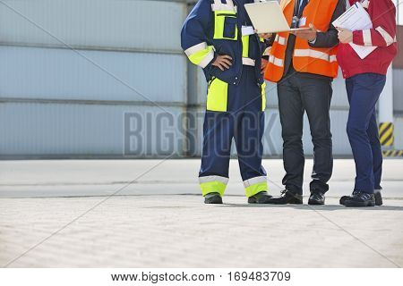 Low section of workers discussing in shipping yard