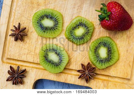 Kiwi fruit cut in slices on wooden cutting board