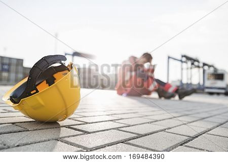 Yellow hardhat at shipyard with depressed male worker in background