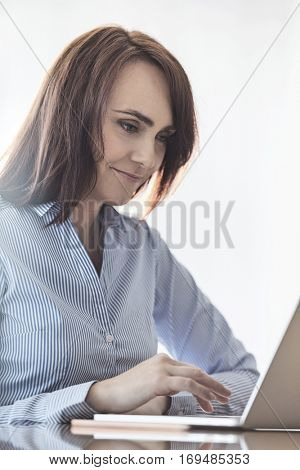 Mid-adult businesswoman using laptop at desk in office