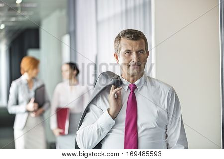 Businessman holding coat over shoulder with female colleagues in background at office