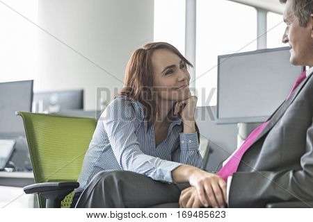 Loving business couple looking at each other in office