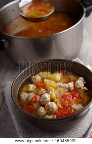 Meatball soup  with vegetables on a rustic table