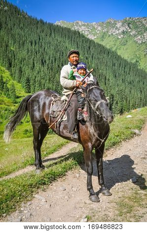 Father And Child On Horse In Kyrgyzstan
