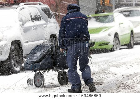 BRONX NEW YORK -JANUARY 7: Mail man pushes mail carriage during snow storm. Taken January 7 2017 in New York.
