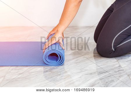 Close-up of attractive young woman folding blue yoga or fitness mat after working out at home in living room. Healthy life keep fit concepts.