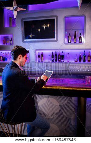 Man using digital tablet at bar counter in bar
