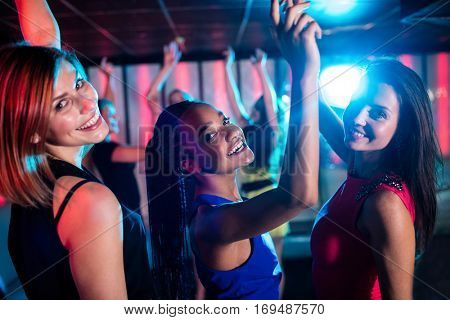 Portrait of smiling friends dancing on dance floor in bar