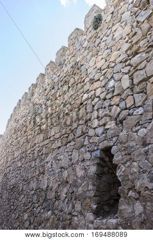 Stone walls of a medieval castle. Town of Consuegra in the province of Toledo, Spain