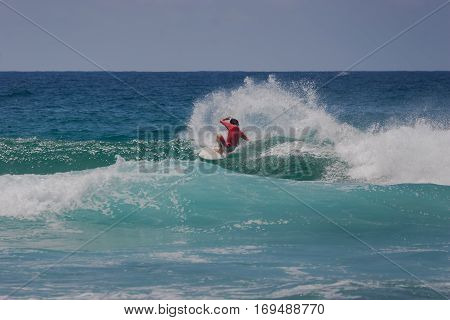 A surfer surfing in the waves doing a cutback manoeuvre