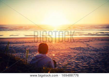 Artistic impression of a boy watching a sunset over the ocean featuring an image from the back intentionally bluring of scenery in the distance.