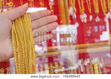 Lot of necklaces gold jewelry in hand at shop
