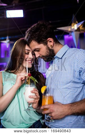 Couple embracing each other at bar counter while having cocktail in bar