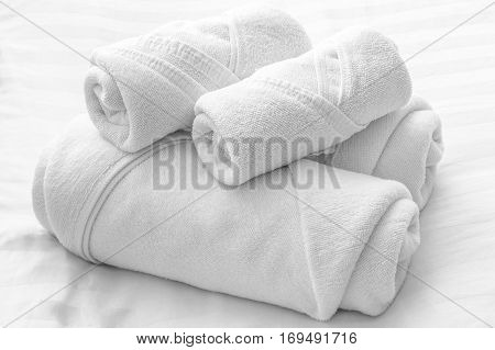 Rolls of white towels laying on white bed
