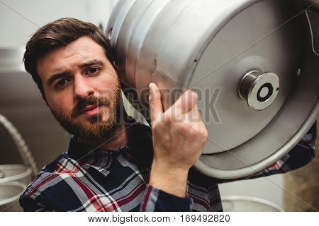 Portrait of young manufacturer carrying keg in brewery