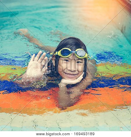 Happy Asian girl swimming in swimming pool