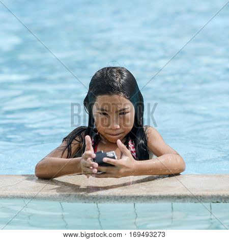 Asian girl girl in water in swimming pool with action camera in protective waterproof underwater photo shooting