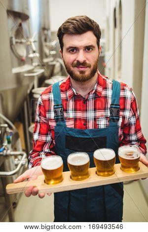 Portrait of manufacturer holding beer samples at distillery