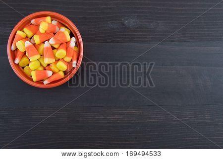 Orange Bowl of Candy Corn on Dark Wooden Background