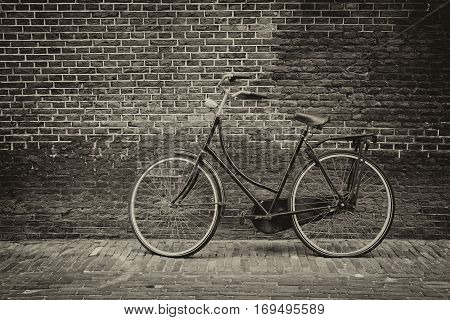 Vintage bike against grunge old brick wall (Sepia tone)