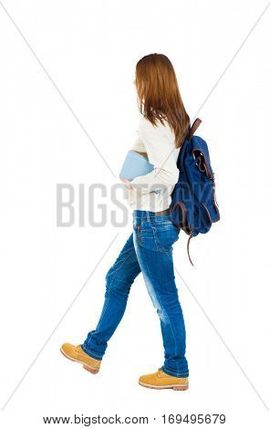 Girl with a backpack on his back is a stack of books. back view. Rear view people collection.  A girl in a white blouse with a blue backpack carries a book under his arm