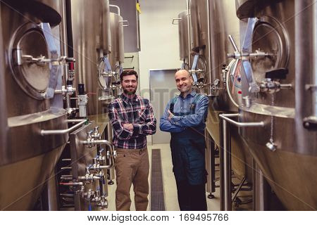 Portrait of confident worker and owner standing amidst machinery at brewery