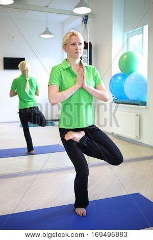 Happy young woman took yoga pose in fitness center in sunny room