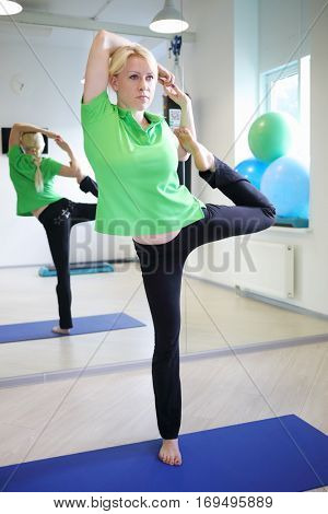 Young woman took yoga pose in fitness center in sunny room with mirror