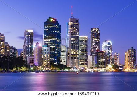View of Brisbane city skyline with illuminated modern buildings and Brisbane river at twilight