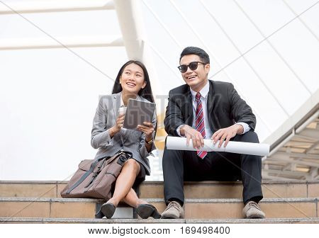 Happy Asian business man and woman sitting on the first step talking about the future. Young co-workers on breaking time relaxing outdoor with the background of urban landscape.