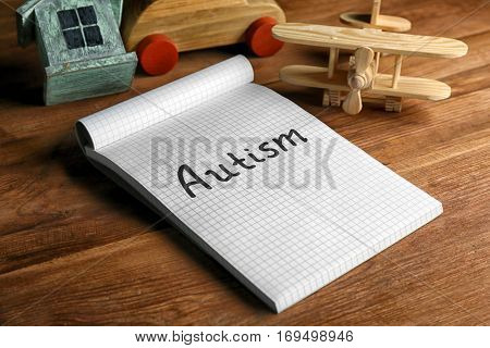 Autism. Word in notebook on wooden background