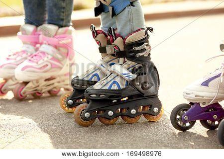 Children on roller skates in park, closeup