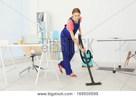 Professional cleaner cleaning floor in office