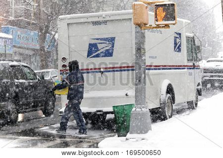 BRONX NEW YORK -JANUARY 7: Mailman with package during snow storm. Taken January 7 2017 in New York.
