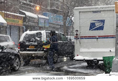 BRONX NEW YORK -JANUARY 7: Mailman carries package for delivery during snow storm. Taken January 7 2017 in New York.