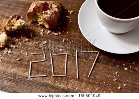 toothpicks forming the number 2017, as the new year, on a rustic wooden table or a wooden bar next to a cup of coffee and a smashed croissant