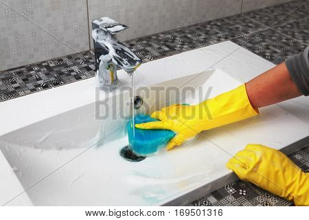 hands of woman in gloves who washes white sink