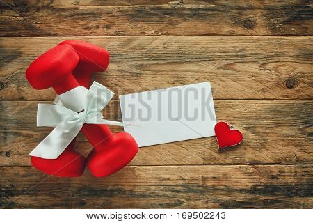 two red dumbbell with a gift bow and blank paper tag heart on wooden planks sport holiday concept