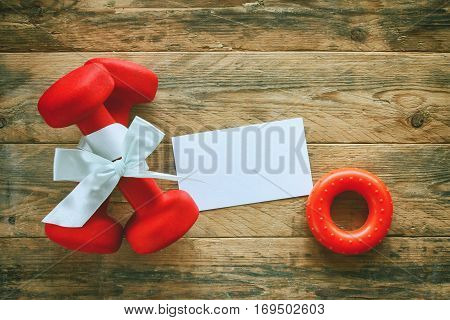two red dumbbell with a gift bow and blank paper tag carpal expander on a wooden planks sport holiday concept