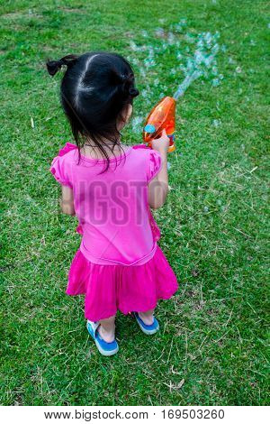 Back View Of Asian Lovely Girl Playing On Green Grass.  Outdoor On Summer Day.