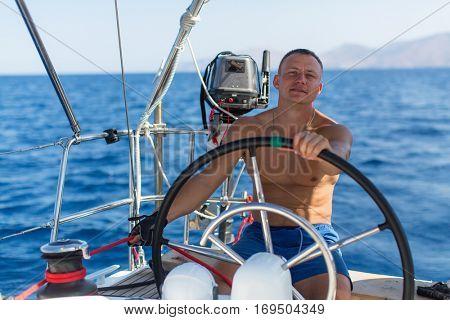 Young man skipper sailing yacht steering wheel. Vacation, sail, holidays, travel.