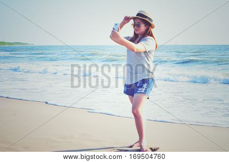 Yong woman traveler relaxing and  taking vacation selfie photograph at the beach. Technical Writing light synthesizer