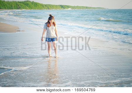 Yong woman traveler relaxing on a perfect beach. Technical Writing light synthesizer. vintage and hipster tone.