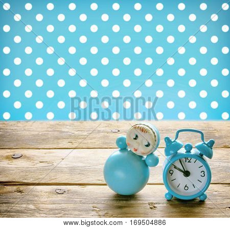 Blue doll roly-poly and old alarm clock on a wooden table retro style