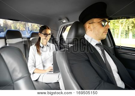 Businesswoman with laptop riding a car with chauffeur